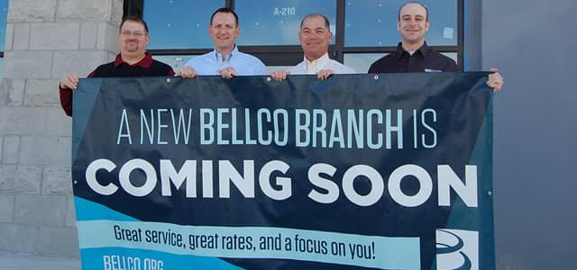 Bellco employees holding a banner to announce a new branch opening