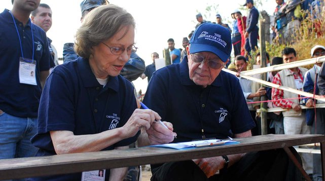 Photo of President Jimmy Carter signing a paper in Nepal