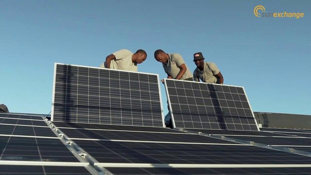 Photo of workers installing solar panels