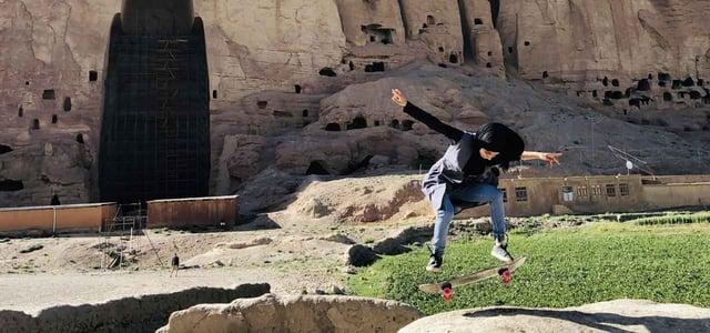 A Girl Kickflips Onto a Rock