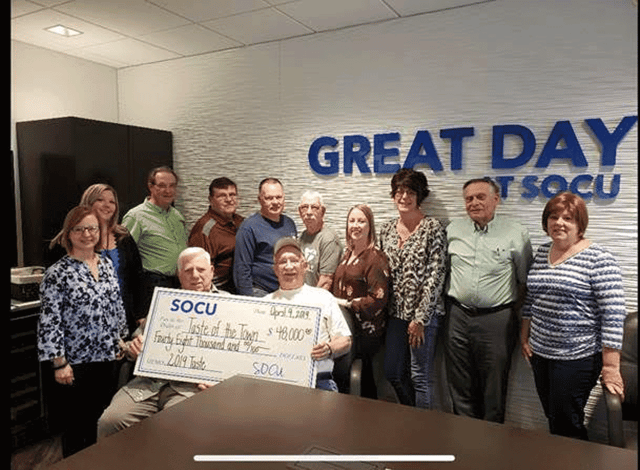 Photo of the SOCU Team Holding a Check