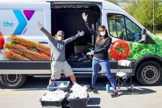 Photo of YMCA workers distributing food in a van