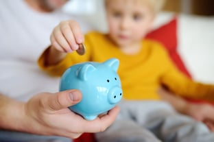 Child Putting Coin in Piggy Bank