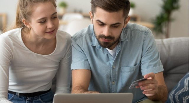 Photo of a woman and man online with a credit card
