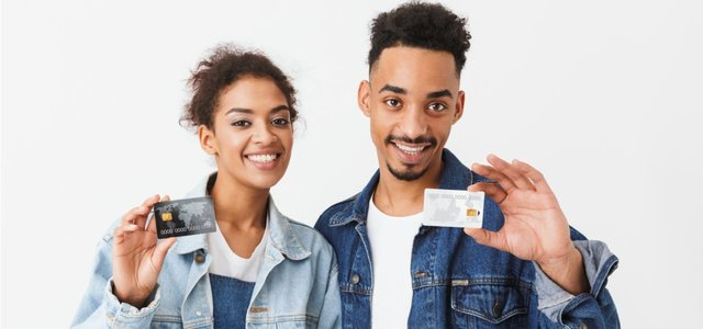 Photo of two people holding up a credit card