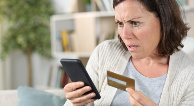 Woman Looking at Phone Holding a Credit Card