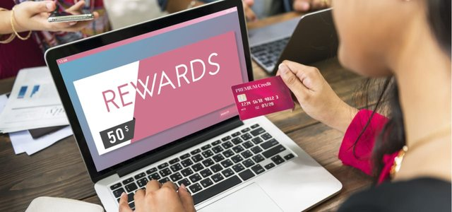 Woman holding a credit card in front of a laptop.