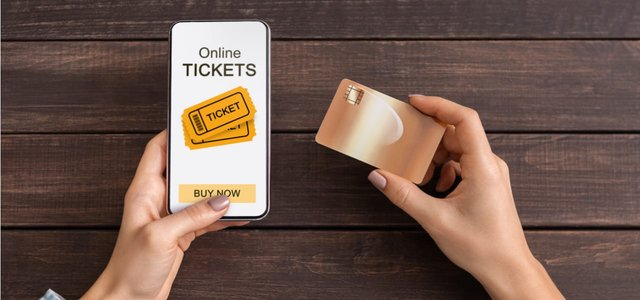 Photo of a woman purchasing tickets on her mobile device with a credit card.
