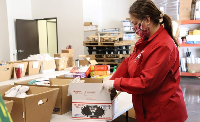 Photo of a Soldiers' Angels volunteer assembling a care package