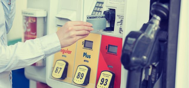 Photo of a woman inserting a credit card to pay at a fuel pump.
