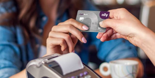A photo of a woman using the Ally CashBack Credit Card