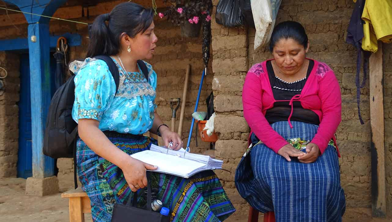 Photo of Carter Center liaison helping a woman in Guatemala