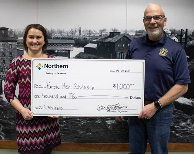 Photo of Alexa Bennett posing with Northern CU scholarship check