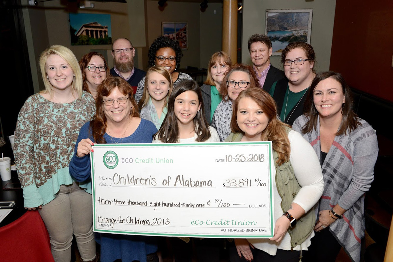 Photo of eCO employees holding the 2018 donation made to Children's of Alabama