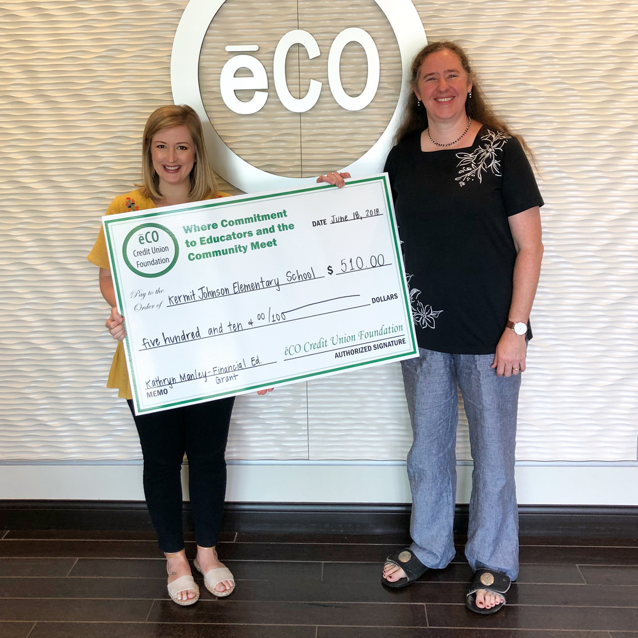 Photo of Melissa Stewart, eCO's Marketing Director, presenting Kathryn Manley with a financial education grant.
