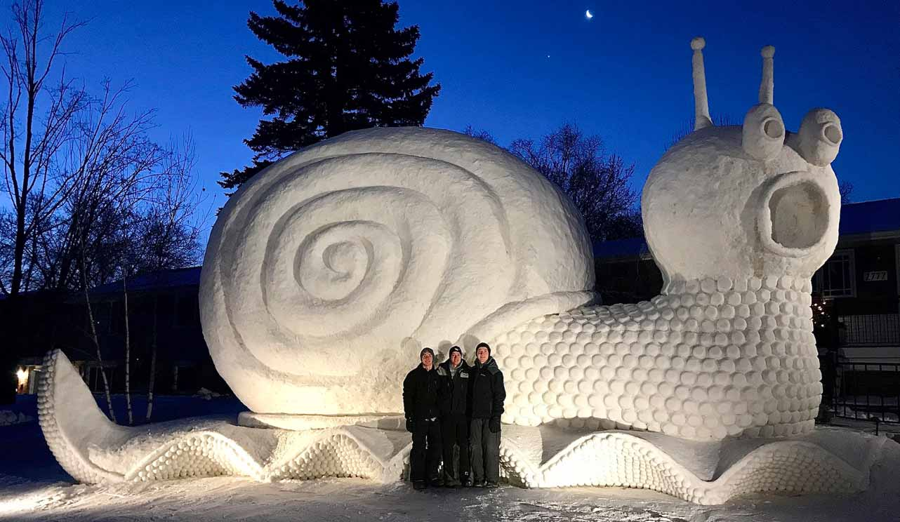 Photo of the Bartz brothers with snail snow sculpture