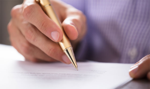 Image of a Person Signing a Form