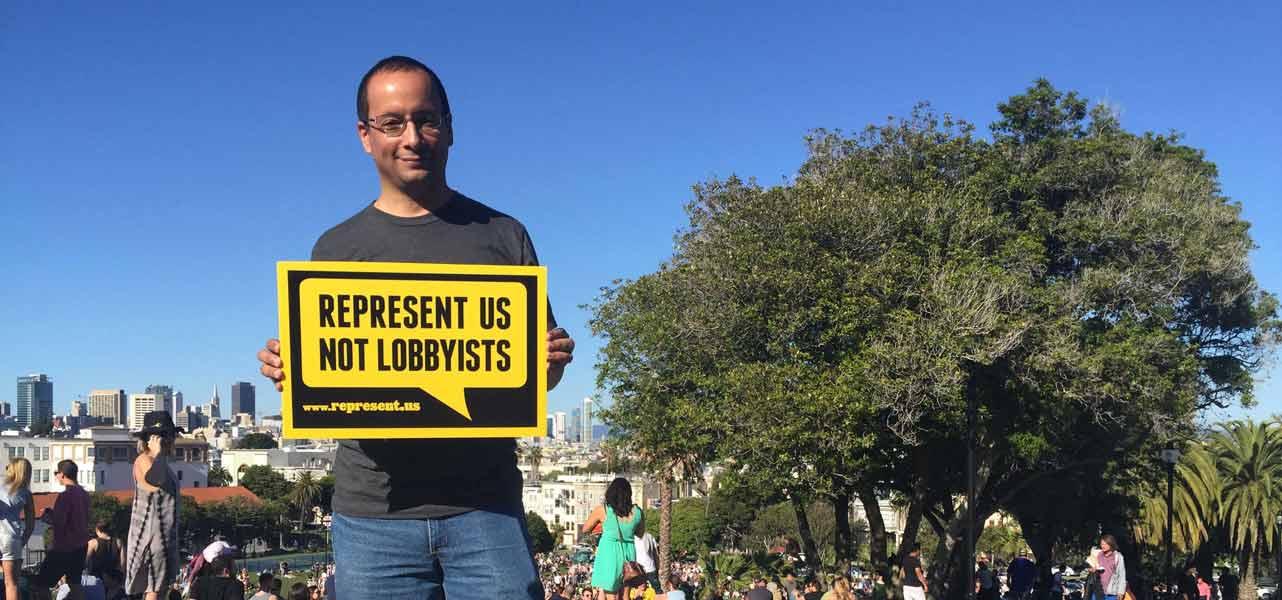 Photo of man holding up RepresentUs sign